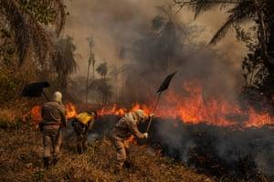 Firefighters combat a fire at the São Francisco de Perigara farm