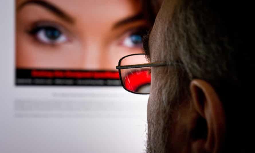 A man looking at an attractive woman on an internet dating site.