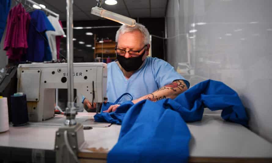 A volunteer tailoring scrubs