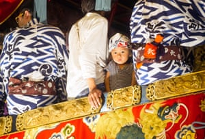 A child on top of a traditional wooden float during the annual Gion Festival in Kyoto, Japan.