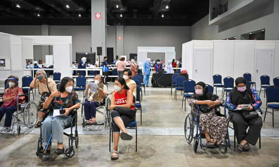 People wait at a mass coronavirus vaccine centre at the Malaysia International Trade and Exhibition Centre in Kuala Lumpur on 31 May.