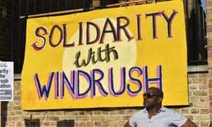 Man with Windrush poster