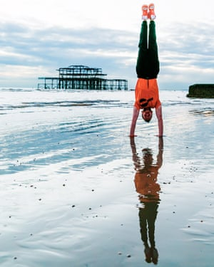 Personal trainer Aslan Steel does a handstand on Brighton beach