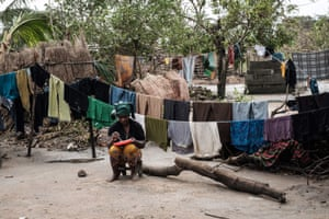 A woman eats lunch after washing clothes in Beira