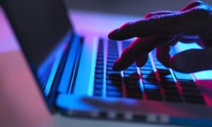 Hand typing on laptop keyboard at night