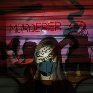 A 24-year-old protester, who identified herself as Kathy, poses as a projector displays a photograph taken during the unrest in Hong Kong