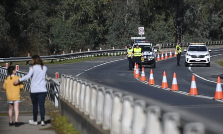 NSW Police officers are seen at the NSW-Victoria border crossing in Howlong near Albury