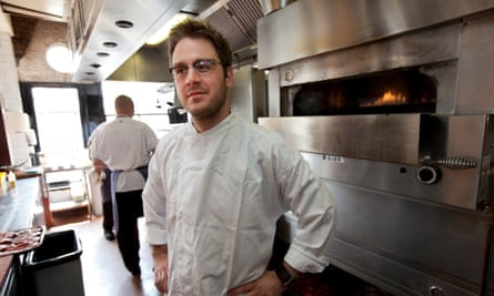 MasterChef winner Tim Anderson in chefs overalls in front of a restaurant oven.