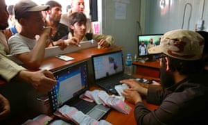 Mosul residents queue to receive authorised CDs from Islamic State members in a photograph from a militant website.