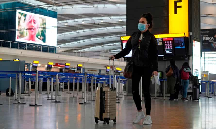 A traveller wearing a face mask walks with her luggage in the departures hall at Heathrow Terminal 5