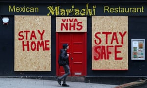 A person passes a boarded up restaurant in Edinburgh which has been painted with an NHS supporting message.