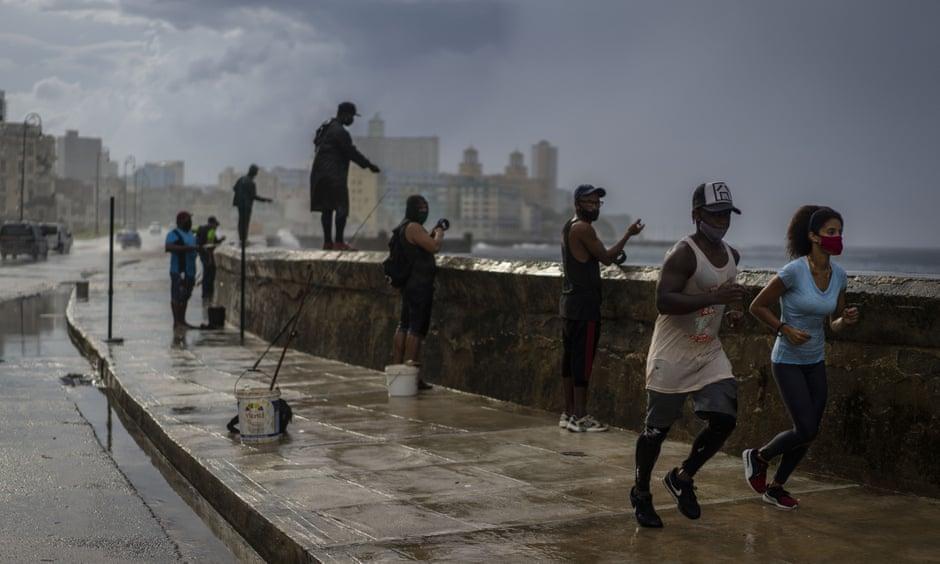 Joggers and fishermen in the rain on the Malecon, Havana's famous sea wall. Photograph: Ramón Espinosa/AP