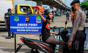 An Indonesian official at a checkpoint questions a scooter rider trying to leave Jakarta.