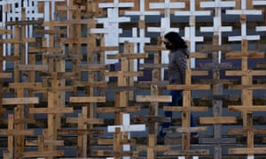A woman wearing a mask walks among hundreds of crosses set up in front of the Parish Church of Our Lady of Loreto to commemorate Holy Week and as a memorial to the victims of coronavirus in the village of Ghajnsielem on the island of Gozo, Malta.