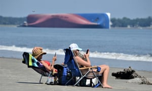 Sunbathers at Jekyll Island's Driftwood Beach off the Georgia coast Sunday.