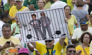 An anti-corruption protester holds a poster with Dilma Rousseff and Lula in prison stripes.