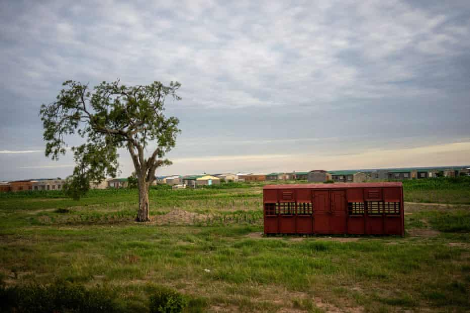 A makeshift ticket office made out of an old carriage sits in a field near the township of Cowdray Park