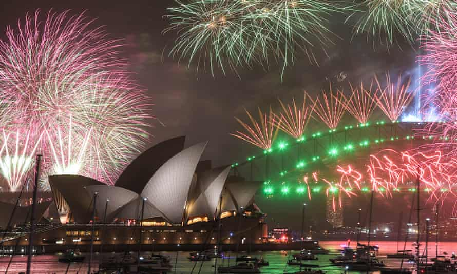 the sydney opera house and sydney harbour bridge underneath coloured fireworks on new year's eve