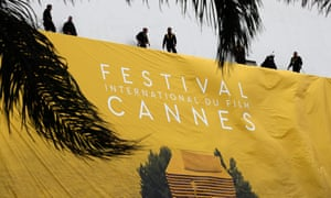 Workers set up a banner of the official poster of the Cannes Film Festival