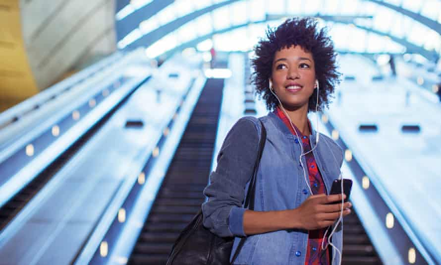 woman listening to earbuds on escalator