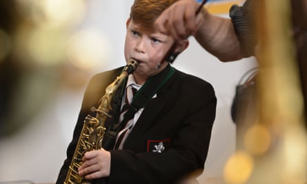 A schoolboy playing a saxophone