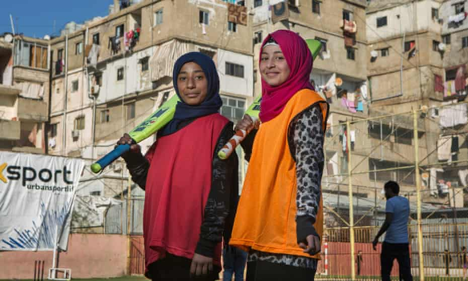 Amali Ibrahim Abed, left, and Shayma Awad, both from Syria, with the apartment blocks of Shatila refugee camp visible in the background.