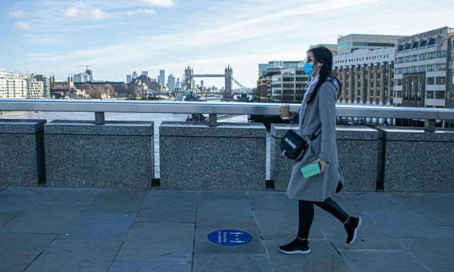 Masked woman walking alone across bridge in London