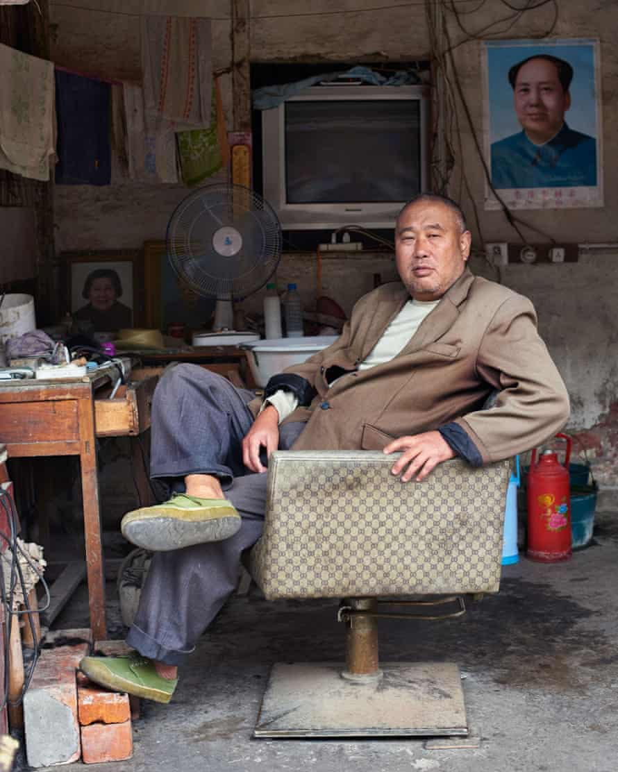 The town barber awaits customers in his 'salon', China
