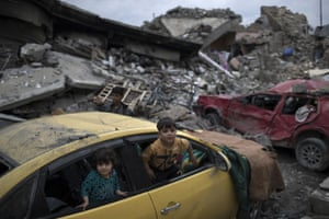 Children play inside a damaged car in a neighbourhood recently retaken by Iraqi security forces from Islamic State militants on the western side of Mosul.
