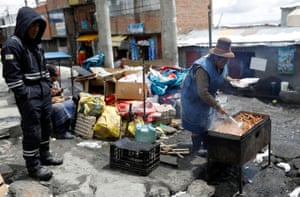 A miner waits for a food vendor to cook him some chicken that he bought on a street in La Rinconada