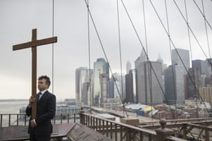 Framed by lower Manhattan, Vladimir Kuzmin carries the cross during a procession on Brooklyn bridge, New York.