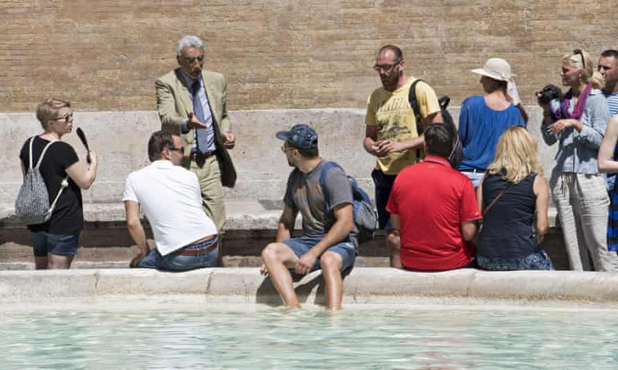 A tourist bathes his feet in the Trevi Fountain in Rome.