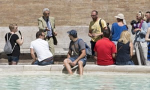 A tourist baths his feet in the Trevi Fountain in Rome.