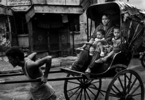 A rickshaw puller with his rickshaw loaded with passengers.