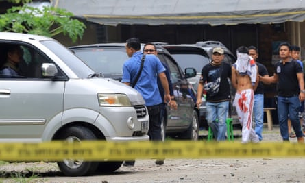 Indonesian police officers accompany the suspect in Medan.