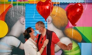 A couple wearing protective face masks hold heart-shaped red balloons in Paris, France.