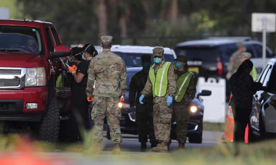 The Florida national guard work at a testing site for the coronavirus as people wait in line in their vehicles, 20 March 2020.