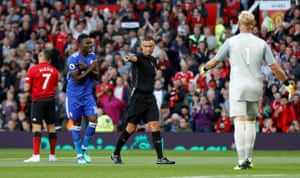 Referee Andre Marriner points to the spot despite the protests from Daniel Amartey.