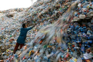 A worker sorts plastic bottles at a recycling centre on the outskirts of Wuhan, Hubei province, China