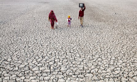 Villagers in Bangladesh walk on a dry river bed.