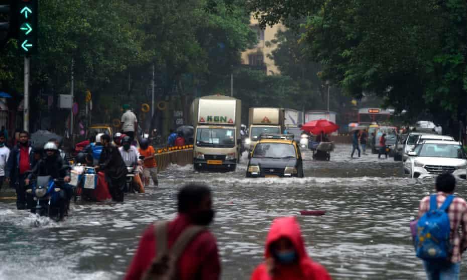 Commuters make their way through a flooded road following heavy monsoon rains in Mumbai.