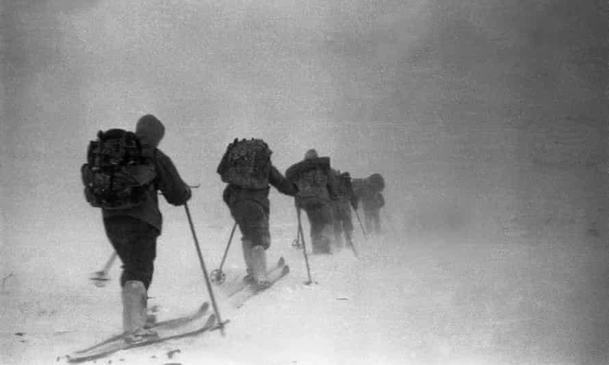 A line of people on skis amid mist and darkness