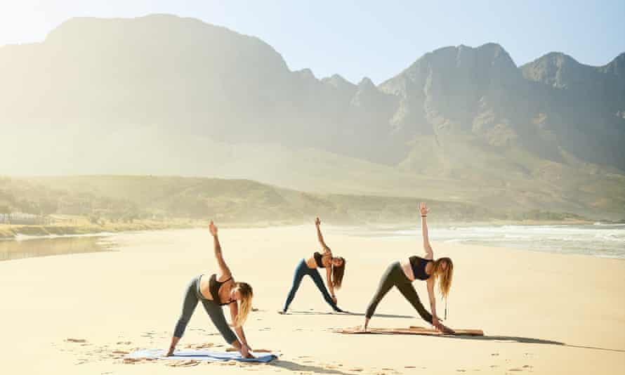 Three young women in dark green tights practicing yoga on the beach