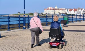 Two elderly women on a promenade: one walking and one riding a mobility scooter