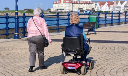 Elderly residents walk on the seafront in Porthcawl, south Wales