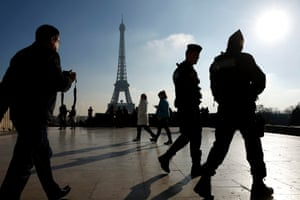 Police officers patrol near the Eiffel Tower in Paris, France