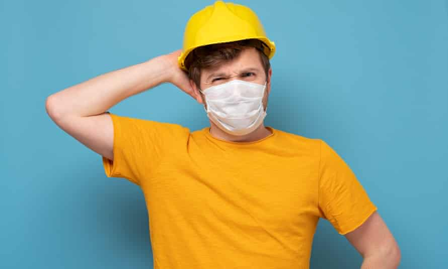 Workman in yellow hard hat and medical mask looking puzzled