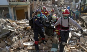 Firefighters remove a body recovered from a destroyed building felled by the earthquake, in Portoviejo, Ecuador, on Monday.