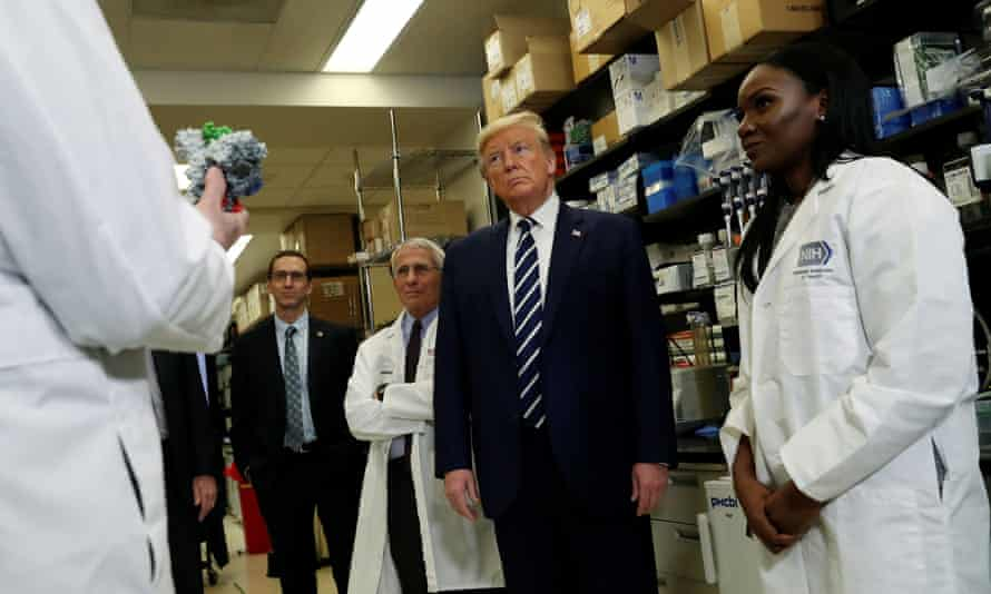 Dr Kizzmekia Corbett, right, a research fellow at the NIH vaccine research center, in Bethesda, Maryland, with Donald Trump in March.