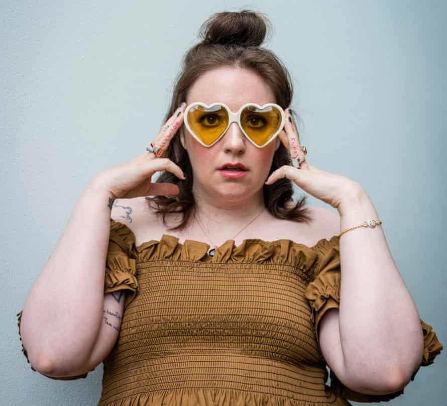 Lena Dunham wearing brown dress and heart-shaped sunglasses